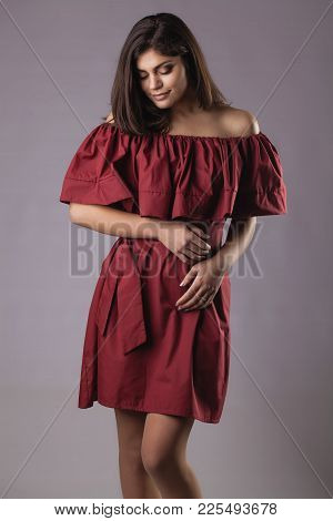 Young Brunette Woman In Red Dress Posing On Grey Background
