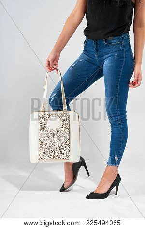 Young Woman With A Stunning Legs Carries White Fashionable Bag With A Stamping And Handles . Also Sh