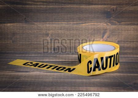 Yellow Caution Tape On A Wooden Background. Safety Barrier For Police Barricade, For Contractors.