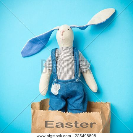 Easter Bunny In A Paper Bag. Blue Background. Easter Ideas. Easter Eggs. Space For Text. Black Lette