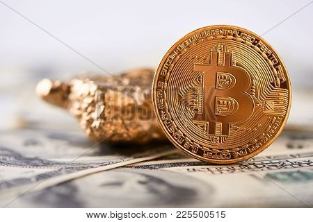 Golden Bitcoin As Main World Cryptocurrency Next To Gold Lump With Blurred Hundred Dollar Banknotes
