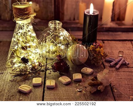 Magic Bottles With Lights, Runes And Black Candle On Witch Table. Occult, Esoteric, Divination And W