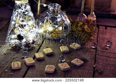 Ancient Runes With Magic Bottles And Crystals On Witch Table. Occult, Esoteric, Divination And Wicca
