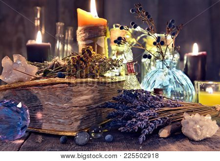Old Witch Book With Lavender Flowers, Crystal And Evil Candles. Occult, Esoteric, Divination And Wic