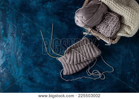 Light Gray Knitting And Knitting Needles, A White Knitted Scarf On A Dark Blue Background. The Conce