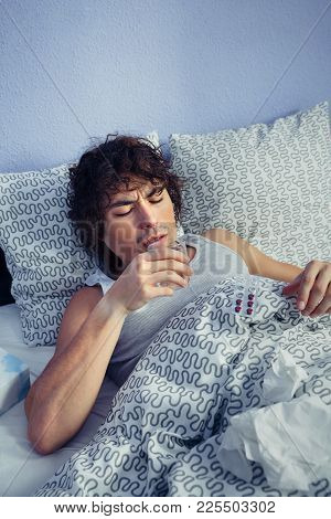 Portrait Of Young Sick Man Drinking Water After Take Medicines Lying On Bed. Sickness And Healthcare