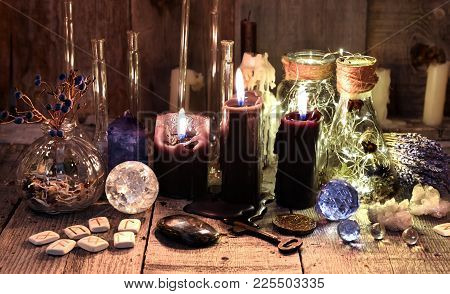 Black Candles With Runes, Crystals, Healing Herbs And Ritual Objects. Occult, Esoteric, Divination A