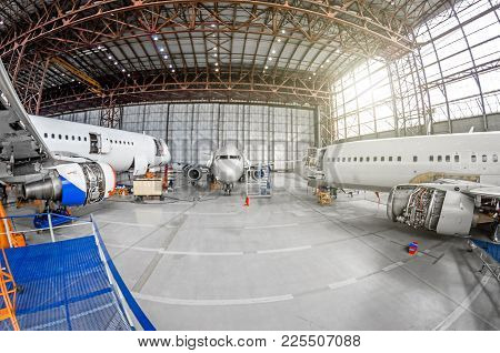 Three Passenger Aircraft On Maintenance Of Engine And Fuselage Repair In Airport Hangar