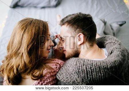 Falling In Love. A Beautiful Young Loving Couple Looks Each Other And Smiling While Sitting In Bed A