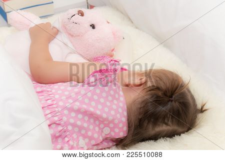 Baby Drinking Water Or Milk From A Small Bottle And Lying On Bed While Hugging Pink Teddy Bear In Th