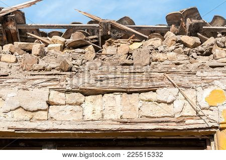 Small Old And Abandoned House Roof Demolished By The Earthquake Destruction Closeup With Blue Sky Ab