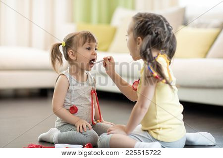 Two Children Girls Playing Doctor At Home. Toddler Girl Opens Her Mouth And Says Aaah. Child Girl Ex