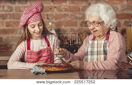 Granny with her little chef girl sprinkle with powder hot homemade pie