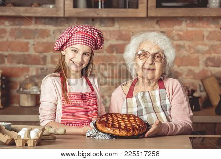 Young little granddaughter with her granny holding a tray and showing homemade fruit pie that they baked together