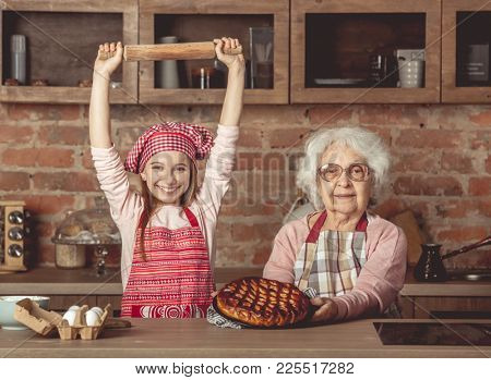 Cheerful grandaughter in chef uniform enjoyed the finished fruit pie with her granny
