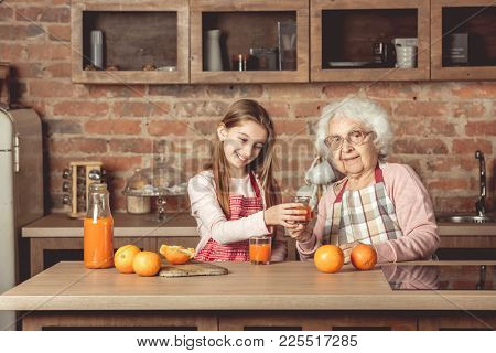 Granny with happy granddaughter tasting and drinking fresh natural orange juice at kitchen at home