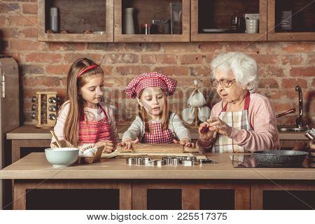 Grandma and granddaughters are spreading dough using a rolling pin