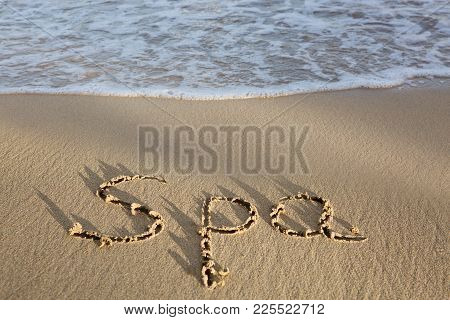 Word Spa Written On The Sand Near The Sea. Wellness Concept Written On Sand.