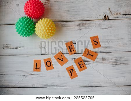 Colored Rubber Squeaky Ball Toys For Pets And Letters Love Pets On White Board Background. Pet Care