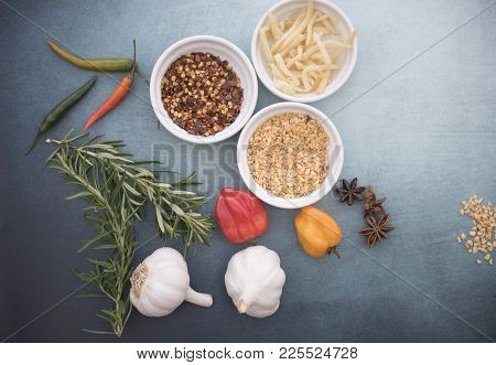 Chilli Seeds, Garlic Flakes, Pieces Of Ginger, Rosemary, Garlic And Chilli Peppers On A Blue Backgro