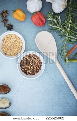Chilli Seeds, Garlic Flakes, Rosemary, Garlic And Chilli Peppers On A Blue Background