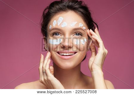 Woman With Moisturizing Cream. Photo Of Beautiful Brunette Woman Touching Her Face On Pink Backgroun