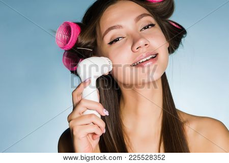 Happy Young Girl Doing Deep Cleansing Of Facial Skin With Electric Brush, On Hair Curler Head