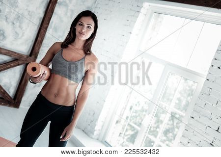 Healthier Than Yesterday. Beautiful Young Woman Smiling Into The Camera While Standing In A Yoga Stu