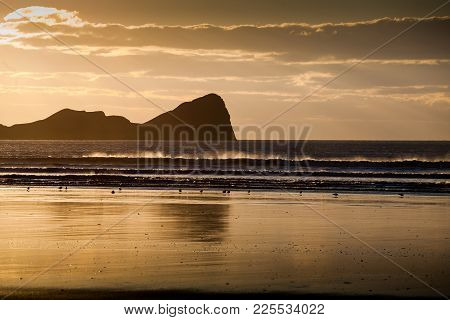 Sunset At Worms Head, An Iconic Piece Of Land Jutting Out From Rhossili Bay On The Gower Peninsula,