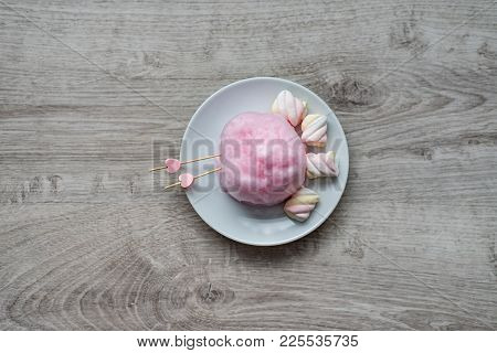 Composition Of Pink Sweet Cotton Wool With Hearts On Wooden Sticks And Colorful Souffle On A Wooden