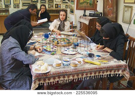 Isfahan, Iran - June 25, 2007: Unidentified Muslim Women Artists In Black Headscarfs Paint Tradition