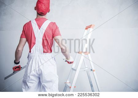 Caucasian Contractor Worker Preparing For Wall Patching Inside Remodeled Apartment.