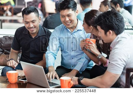 Team of four dedicated employees sitting in front of a laptop while working together at an innovative business project in a modern office