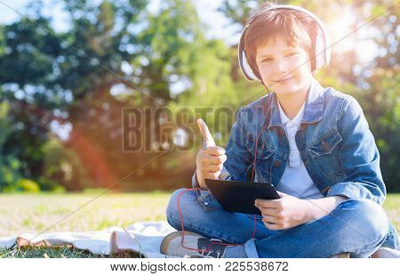 Super Cool. Adorable Little Boy In Casual Showing A Super Sign While Sitting In The Grass And Listen