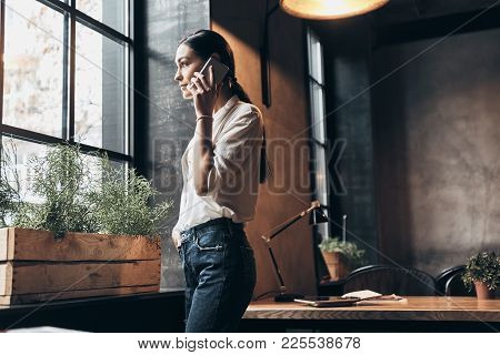 Talking About Business.  Beautiful Young Woman In Smart Casual Wear Talking On Her Smart Phone And S