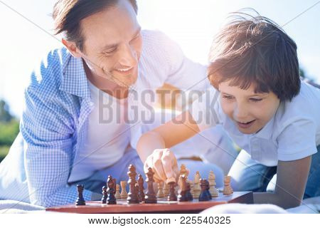 He Is So Smart. Satisfied Adult Man Beaming While Looking At His Little Son Playing Chess And Really