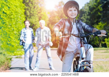 Proud Family Moment. Adorable Boy Grinning Broadly While Riding A Bicycle For The First Time And Get