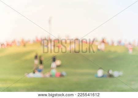 Blurred People At Public Grassy Hill Park In Downtown Houston, Texas, Usa