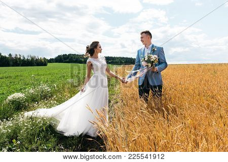 The Bride And Groom Stand In The Field, Holding Hands And Looking At Each Other. A Man Stands In Whe