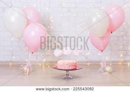 Birthday Celebration Concept - Cake Over Brick Wall Background With Lights And Colorful Balloons