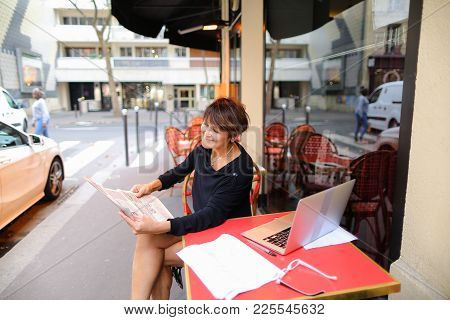 Woman Sitting At Table Of Street Cafe Skimmed Through New Newspaper. Female With Short Haircut Dress