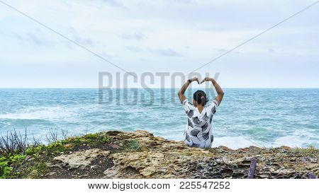 Asian Woman Sitting Lonely On The Rock Looking At The Sea And Making Heart-shaped Arms At Khao Laem