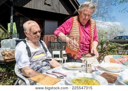 Elderly Woman Serving Her Housband. Active Retirement.