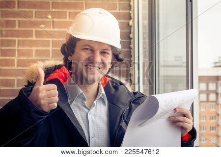 A Handsome Construction Worker Giving A Thumbs-up Sign. Authentic Construction Worker On Actual Cons