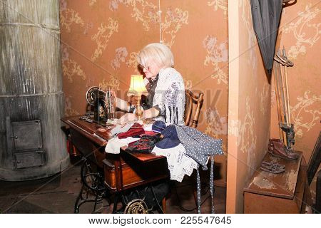 An Elderly Woman Is Behind Sewing.