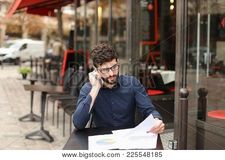 Prosperous Businessman Speaking With Assistant At Cafe Table And Working With Documents. Gladden Man