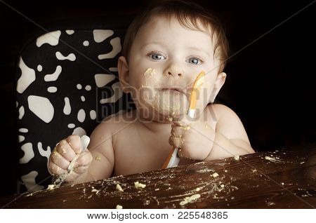 Feeding A Child. Funny Dirty Baby At Meal After Lunch. Close-up Photo On Black Background.