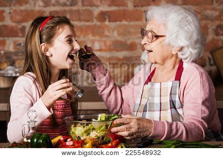 Granny gives to try a tasty vegetable salad to her grandchild