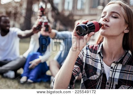 So Delicious. Nice Pleasant Positive Woman Holding A Bottle Of Beverage And Closing Her Eyes While E