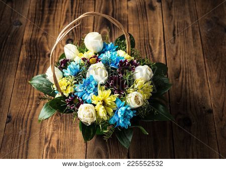 A Basket With Diferent Flowers On A Wooden Background
